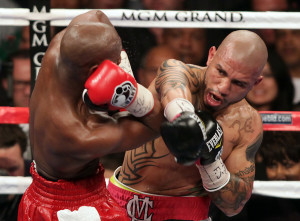 Miguel Cotto (R) grazes Floyd Mayweather